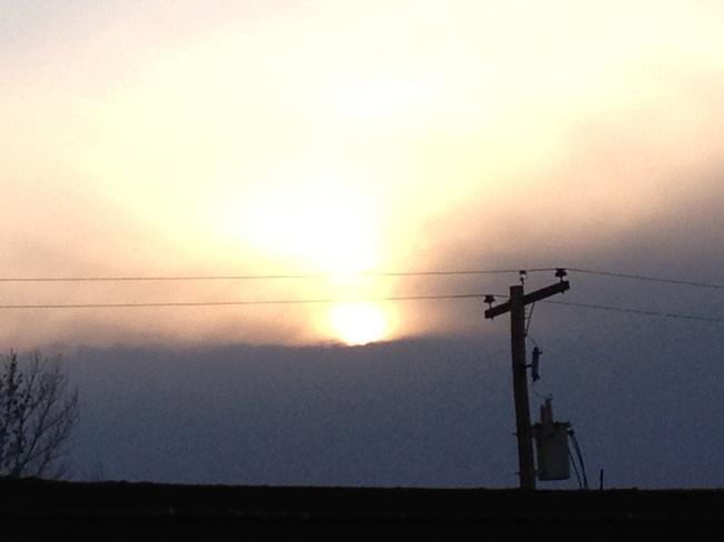 sun behind storm clouds Estevan, Saskatchewan Canada