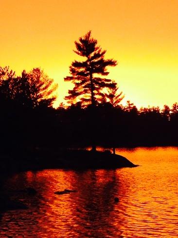 Sunset under dark rain clouds Kahshee Lake, Ontario Canada
