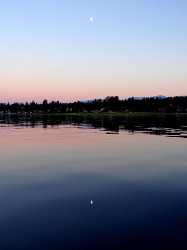Moons reflection in the still eveinng waters Royston, British Columbia Canada
