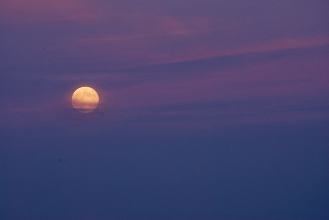 moon rise with setting suns rays behind Pointe-Claire, Quebec Canada