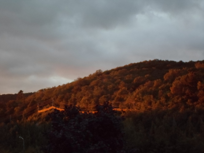 Sunseting shines on hill of trees Elliot Lake, Ontario Canada