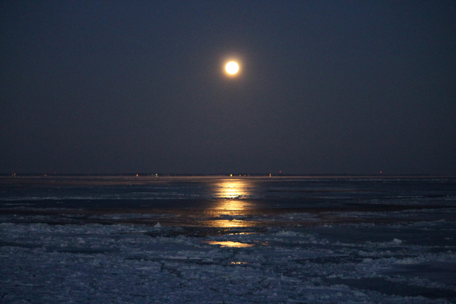 Moon over the icy water Cap-Pele, New Brunswick Canada