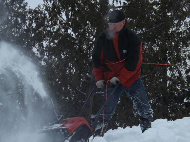 Cleaning snow off the roof Dunchurch, Ontario Canada