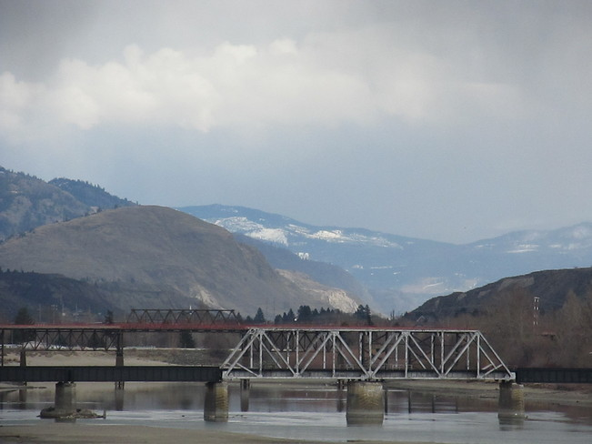 Beautiful rain clouds floating over the South Thompson River with bridges and sn Kamloops, British Columbia Canada