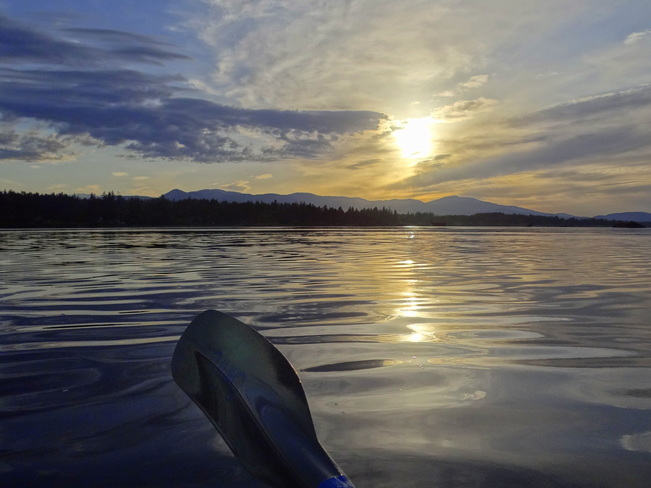 A peaceful nights paddle in the Comox Bay with cloud reflections and a setting s Royston, BC, Canada