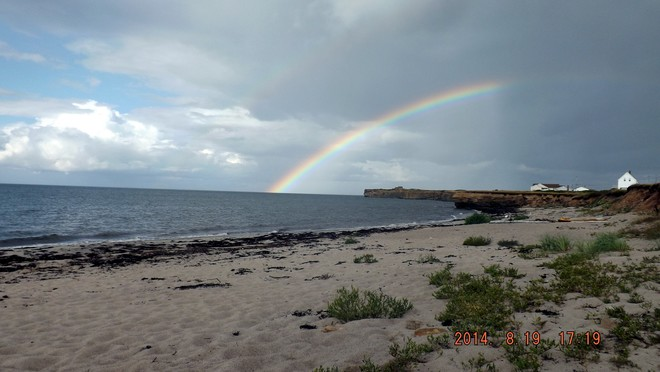 Rainbow just coming out of the ocean at the Lamond street Beach. Sydney Mines, NS