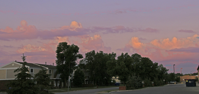 Cumulus clouds in the southwest catch the colors of the sunrise: Winnipeg, MB