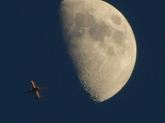 Plane flying by moon