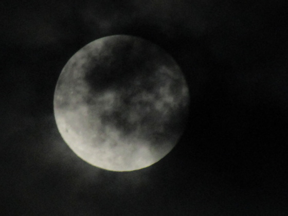 August full moon through the clouds