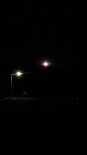 Moon next to a street light