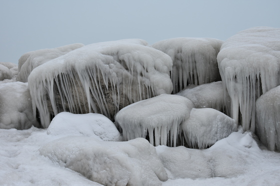 Waves causing lakeshore rocks to be covered in ice
