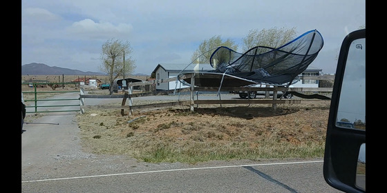 It was very windy in Edgewood. A trampoline blew onto a fence.