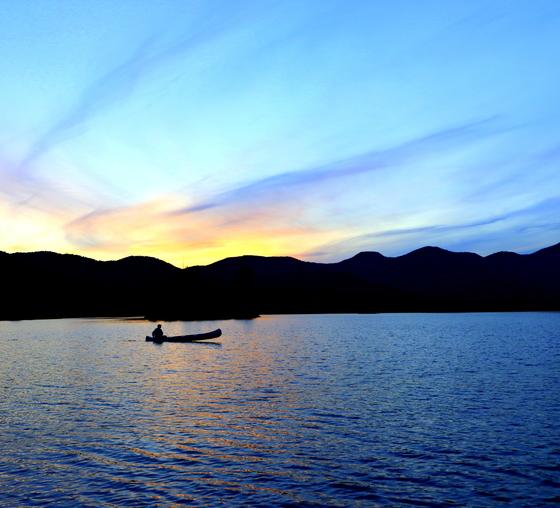 Canoeing on Mountain Lake at Sunset