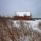 Une ferme rouge dans un champs de neige