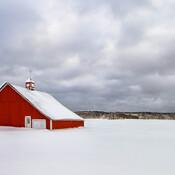 Ferme rouge sur décor hivernal