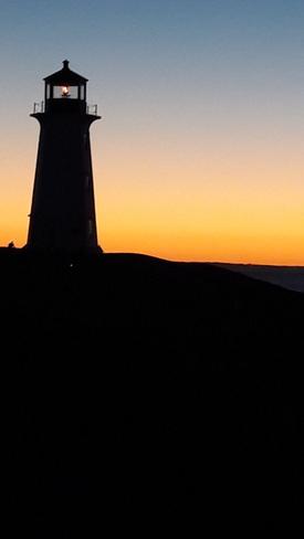 Sunset light igniting Peggys home Peggys Cove, Nova Scotia